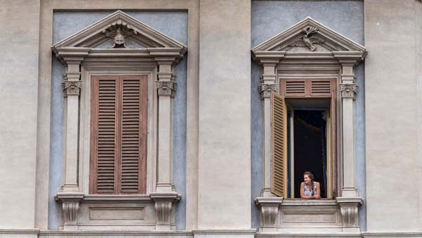 A woman looks out a large orate window in Italy